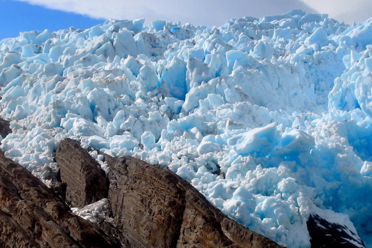 Light blue ice of glacier against dark brown rock