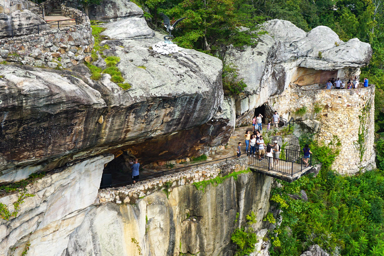 People looking out from cliff ledges on a mountainside