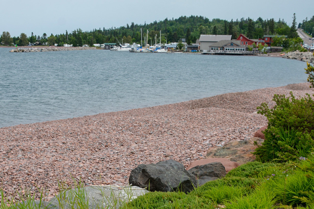 Gravel beach along lake with town in distance