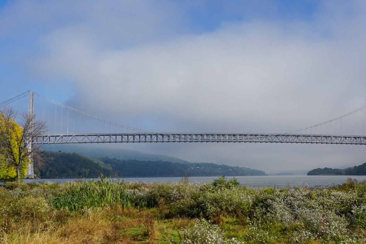 Long span bridge across a river with mountains on both sides