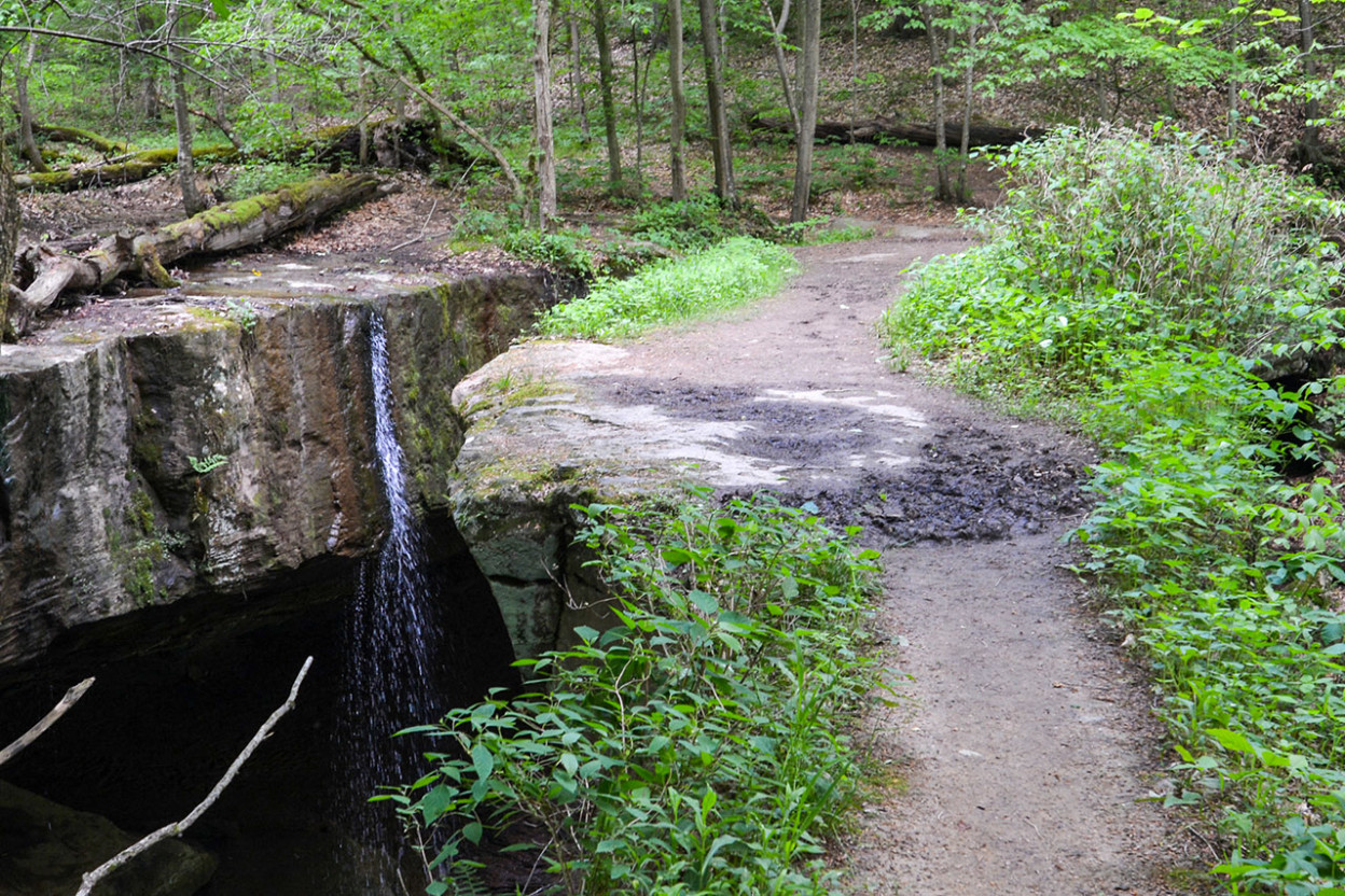 Trail with crevices on both sides and waterfalls on the left