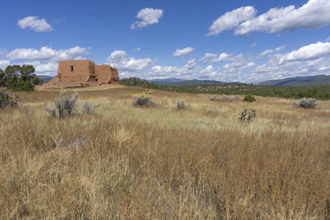 Ruins of clay-colored Spanish Mission on a hill with mountains beyond