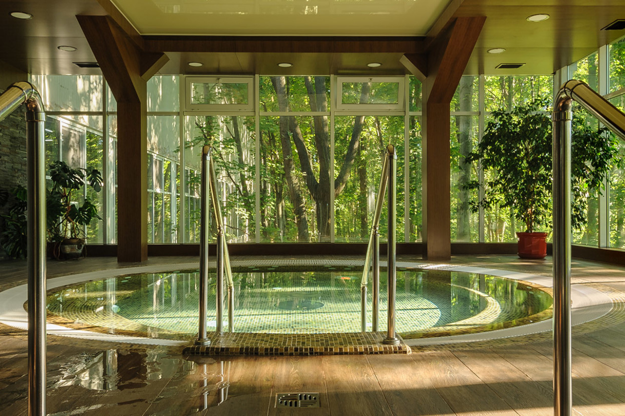 Big round jacuzzi bath in building overlooking woods